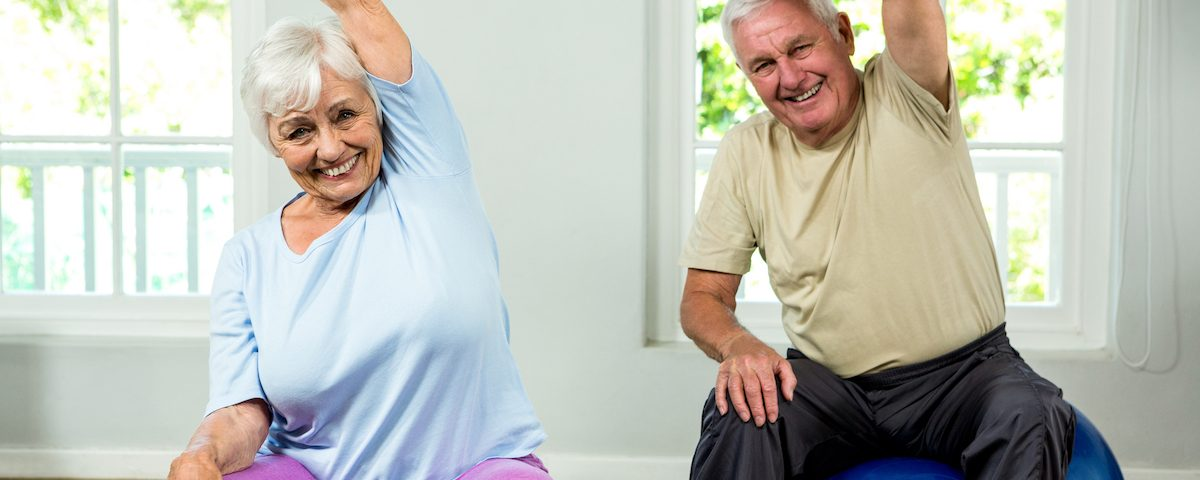 Portrait of smiling senior man and woman exercising at health club
